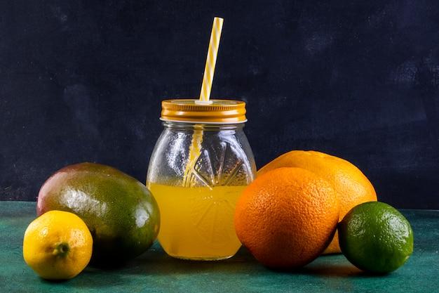 Vooraanzichtmango met citroenkalksinaasappel en sap in een kruik met een geel stro