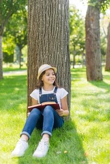 Vooraanzichtmeisje dat met boek weg kijkt