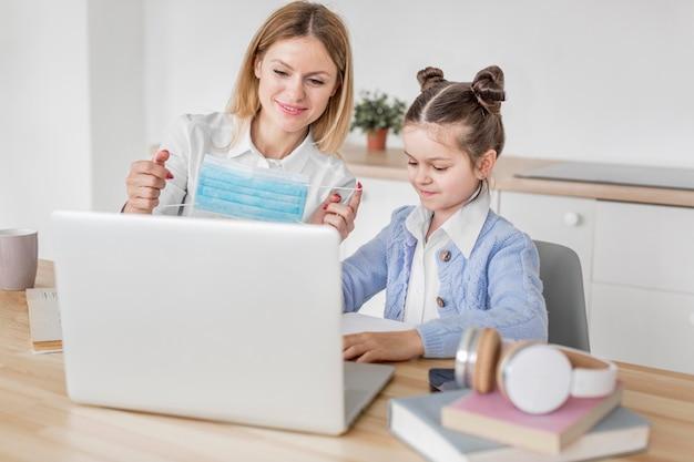 Vooraanzichtmeisje dat thuis met haar leraar bestudeert