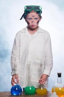 Vooraanzichtmeisje met laboratoriumjas en glazen