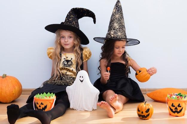 Vooraanzichtmeisjes die op vloer op halloween zitten