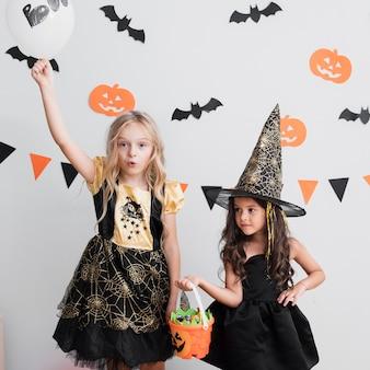 Vooraanzichtmeisjes in heksenkostuum voor halloween