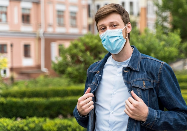 Vooraanzichtmens die een gezichtsmasker buiten met exemplaarruimte draagt
