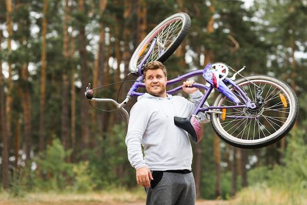 Vooraanzichtmens die fiets steunt