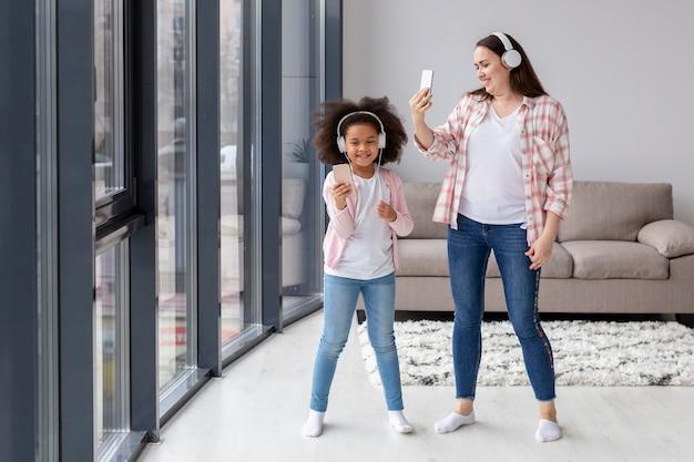 Vooraanzichtmoeder en dochter die selfies thuis nemen