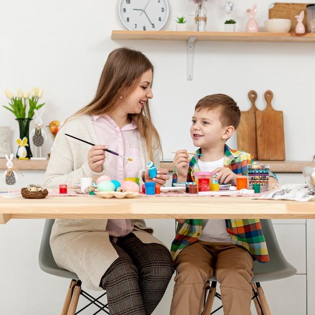 Vooraanzichtmoeder en zoon die samen eieren schilderen voor pasen
