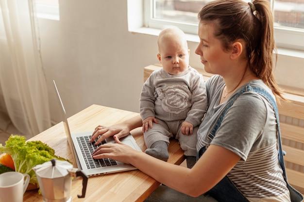 Vooraanzichtmoeder met baby thuis