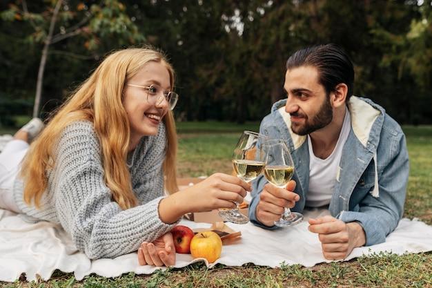 Vooraanzichtpaar dat een glas wijn buiten heeft