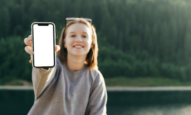 Vooraanzichtportret van glimlachende vrouwelijke reiziger die het lege scherm van de smartphone toont