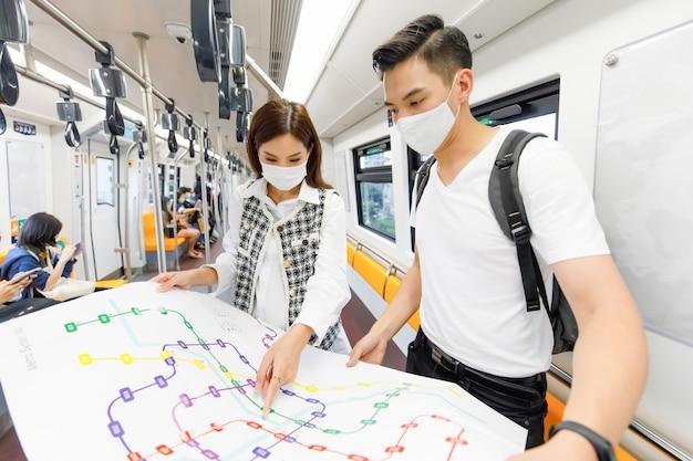 Vooraanzichtportret van jonge volwassen aziatische paartoeristen met een medisch masker die staan en de papieren metrokaart bij elkaar houden in de skytrain met een wazige kaartvoorgrond en skytrain-achtergrond