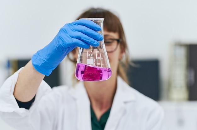 Vooraanzichtportret van jonge vrouw die een pinkvloeistof in een erlenmeyer-fles bekijken. vrouwelijke wetenschapper concept. focus op glas / handschoen