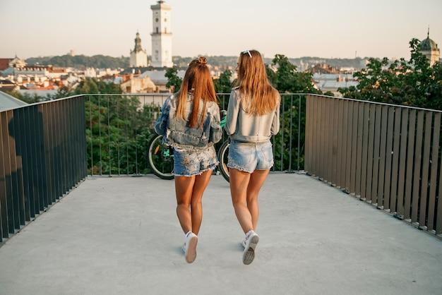 Vooraanzichtportret van twee gelukkige vrienden die en bij zonsondergang in een park lopen spreken