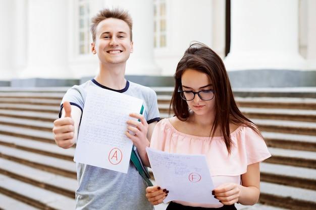 Vooraanzichtportret van twee studenten die mislukte en goedgekeurde examens tonen die zich dichtbij conventionele universiteit bevinden