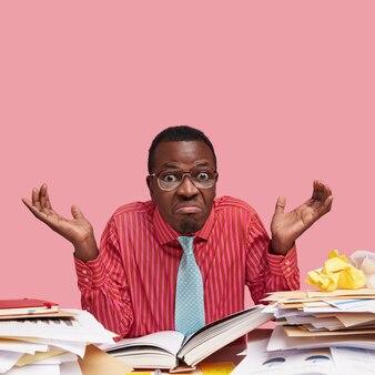 Vooraanzichtportret van verwarde zwarte zakenman met donkere huid, grappige blik, haalt schouders op, vraagt zich iets af