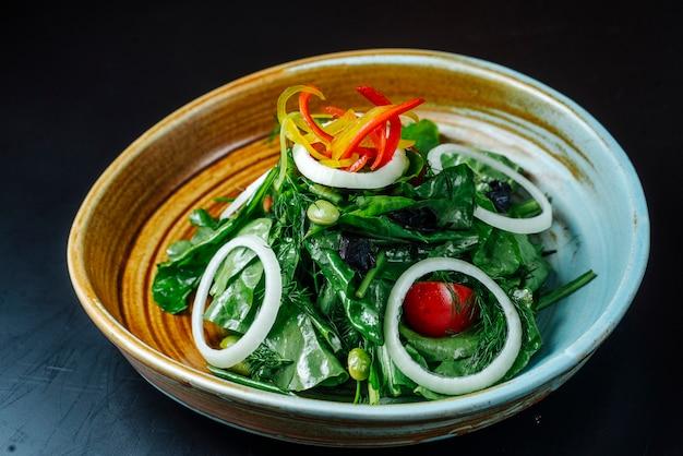 Vooraanzichtsalade van greens met uientomaten en paprika's op een plaat