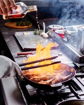 Vooraanzichtschotel die bradend vlees binnen ronde pan op de keuken koken