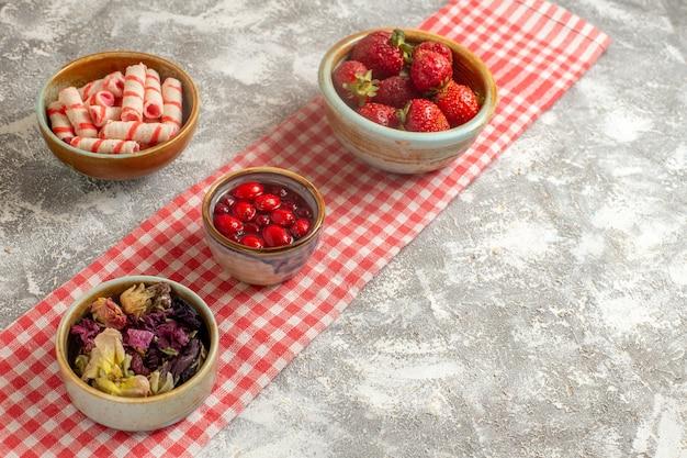Vooraanzichtsuikergoed en gelei met aardbeien op de witte zoete bloem van het oppervlaktesuikergoed