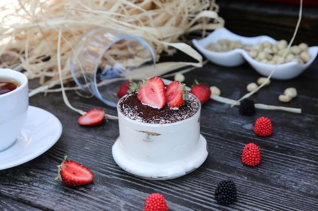 Vooraanzichttiramisu in een kop met aardbeien op de lijst