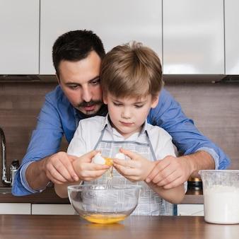 Vooraanzichtvader die zoon helpt om eieren te barsten