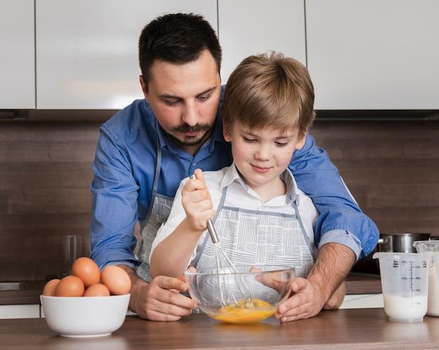 Vooraanzichtvader en zoon die eieren mengen
