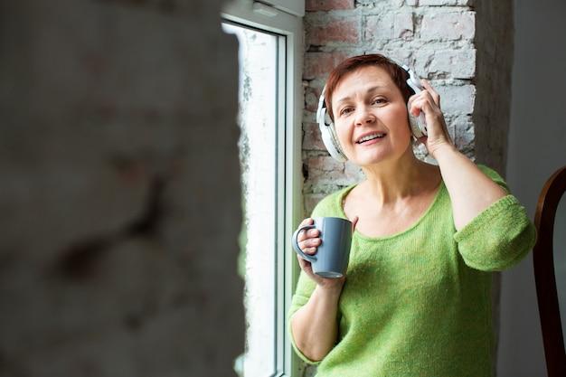 Vooraanzichtvrouw bij venster het luisteren muziek