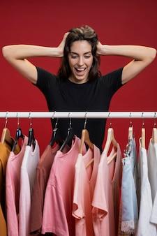 Vooraanzichtvrouw die door kleren in een winkel kijkt