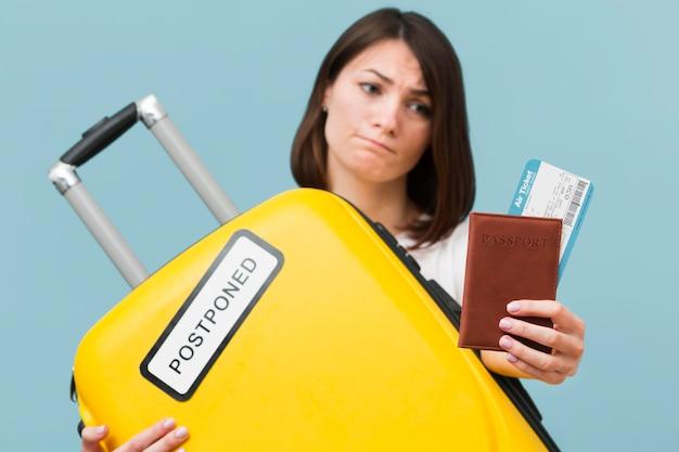 Vooraanzichtvrouw die een gele bagage met een uitgesteld teken houdt