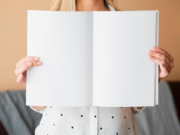 Vooraanzichtvrouw die een modeltijdschrift houdt