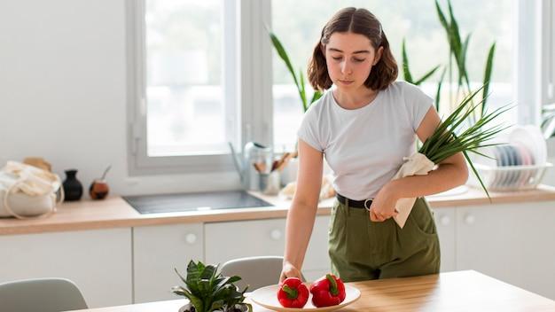 Vooraanzichtvrouw die groenten thuis schikken