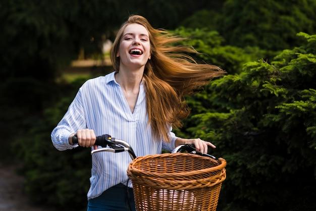 Vooraanzichtvrouw die haar fiets berijdt