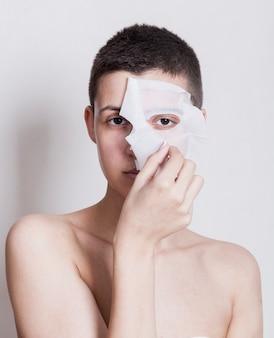 Vooraanzichtvrouw die haar gezichtsmasker opstijgt