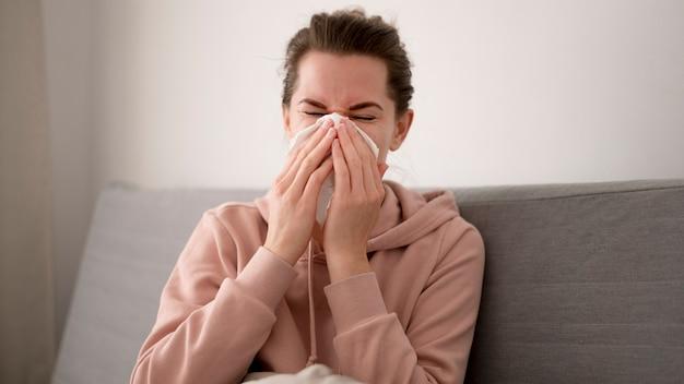 Vooraanzichtvrouw die haar neus blaast