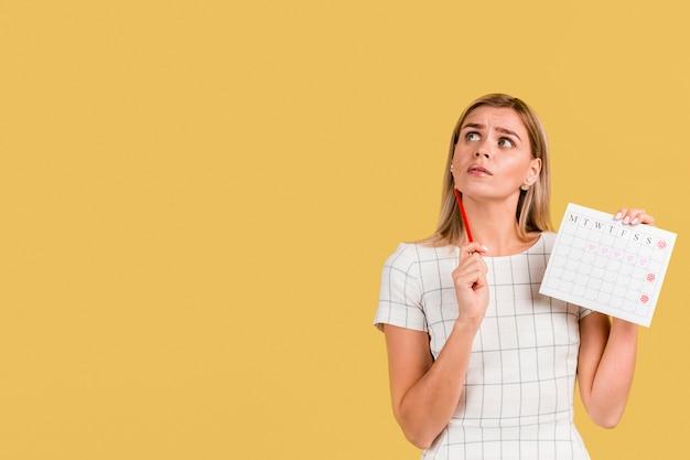 Vooraanzichtvrouw die haar periodekalender met exemplaarruimte toont