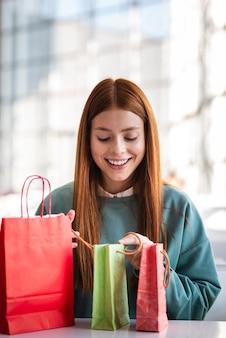 Vooraanzichtvrouw die het winkelen zakken onderzoekt