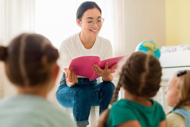 Vooraanzichtvrouw die iets voor haar studenten leest