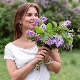 Vooraanzichtvrouw die lila boeket ruiken