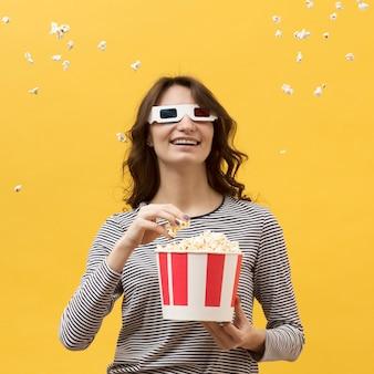 Vooraanzichtvrouw die met 3d glazen een emmer met popcorn houden