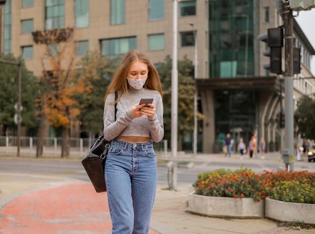 Vooraanzichtvrouw die met medisch masker haar telefoon controleert