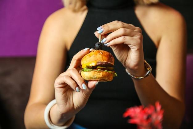 Vooraanzichtvrouw die miniburger met olijf eten