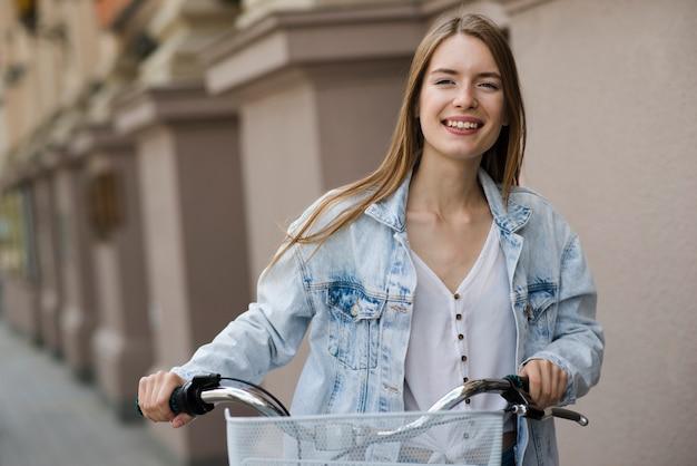 Vooraanzichtvrouw die naast fiets loopt