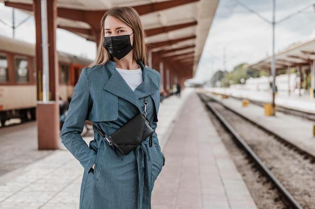 Vooraanzichtvrouw die op de trein wacht