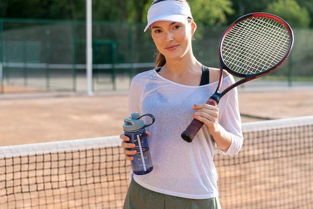 Vooraanzichtvrouw die op tennisbaan hydrateert