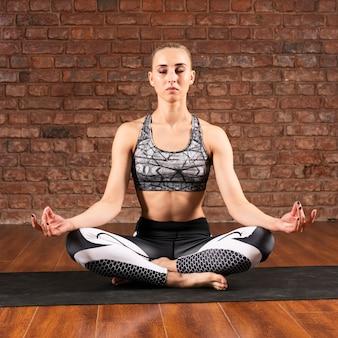Vooraanzichtvrouw die thuis mediteren