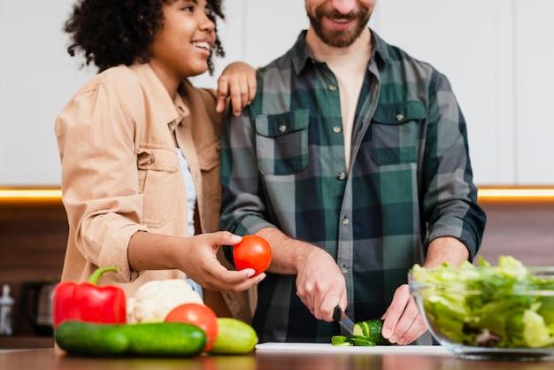 Vooraanzichtvrouw die tomaat en man scherpe groenten houden