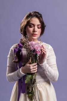Vooraanzichtvrouw die van een boeket van bloemen geniet