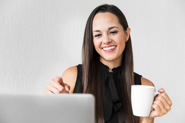Vooraanzichtvrouw die van haar kop van koffie genieten op het kantoor