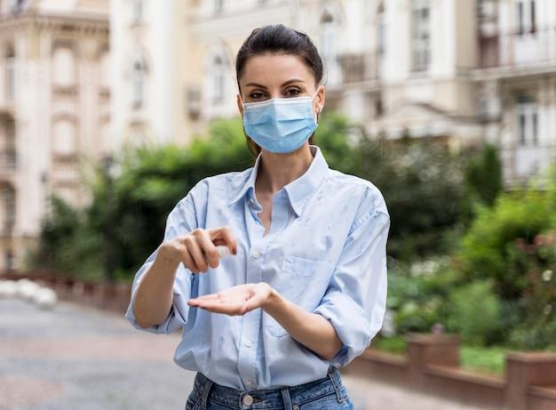 Vooraanzichtvrouw die zijn handen desinfecteert