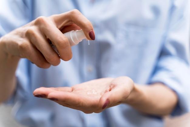 Vooraanzichtvrouw die zijn handenclose-up desinfecteert