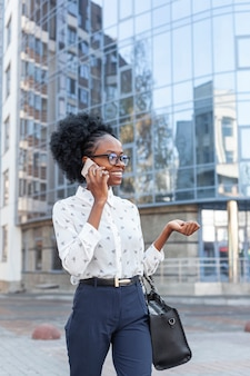 Vooraanzichtvrouw met handtas die over telefoon spreekt