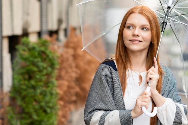 Vooraanzichtvrouw met paraplu in openlucht